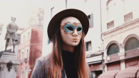 disfarçar : Woman with long hair and hat wearing a white carnival face mask in Venice street, Italy looking at camera, turning back.