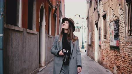 Attractive happy professional female photographer walking with camera smiling along beautiful old street in Venice Italy Stock Footage