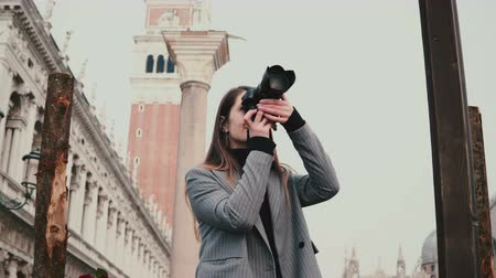 pilares : Attractive professional Caucasian journalist with camera taking photos of ancient buildings in old town of Venice Italy.