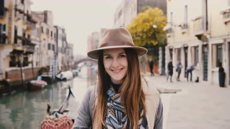 Close-up portrait of happy young beautiful European woman tourist in hat smiling standing by famous Venice canal, Italy. Stock Footage