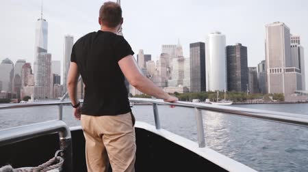 férfias : Handsome excited traveler man with arms wide open enjoying amazing New York skyline on a river tour boat slow motion. Stock mozgókép