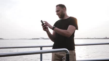 захватывающий : Happy successful Caucasian entrepreneur using smartphone, looking around on a beautiful sunset boat trip slow motion.
