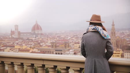 mítosz : Back view of girl in hat standing at observation deck enjoying amazing view of Florence, Italy on cold rainy cloudy day. Stock mozgókép