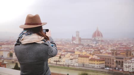 Мария : Happy young female traveler walks up, taking smartphone photo of amazing cityscape panorama of autumn Florence, Italy. Стоковые видеозаписи