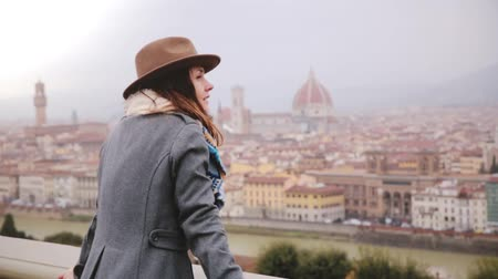 mitologia : Happy smiling tourist girl in warm clothes walks up to enjoy beautiful panoramic view of Florence, Italy on a rainy day.