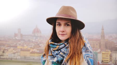 Мария : Portrait of young beautiful Caucasian girl in hat with peaceful mysterious smile, looking at camera in rainy Florence. Стоковые видеозаписи