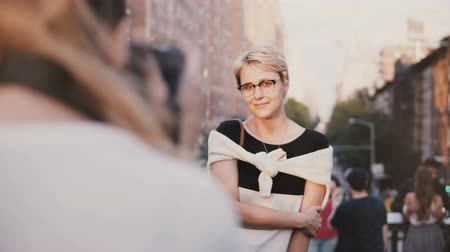 photoshoot : Happy peaceful European blonde girl with short hair in eyeglasses smiling at photoshoot outside, posing at camera. Stock Footage