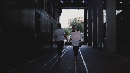 felülnézet : Slow motion back view happy romantic couple walking together holding hands on rails under dark evening city bridge. Stock mozgókép