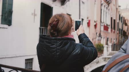 venedik : Back view happy senior female traveller taking smartphone photo of beautiful autumn water canal street in Venice Italy. Stok Video