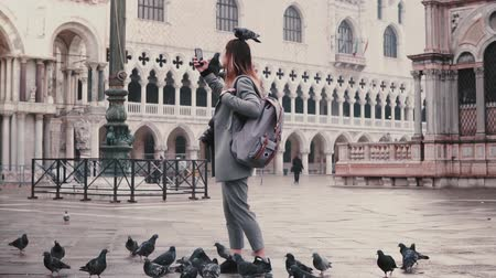 venedik : Happy smiling female tourist with pigeons sitting on her arm and head takes selfie on city square in Venice slow motion.