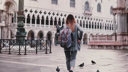 marco : Back view happy fashionable female tourist walks on San Macro square with pigeons sitting on arms in Venice slow motion.