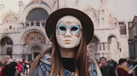 маскарад : Portrait of woman with long hair wearing hat and a carnival mask standing at San Marco cathedral in Venice slow motion. Стоковые видеозаписи