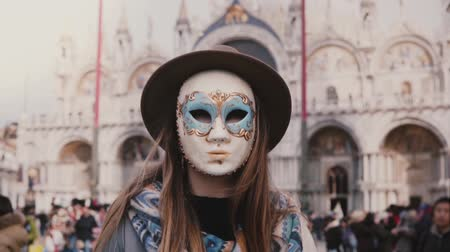 carnaval de venise : Close-up shot of woman with long hair in traditional carnival mask standing at Venice San Marco square slow motion.