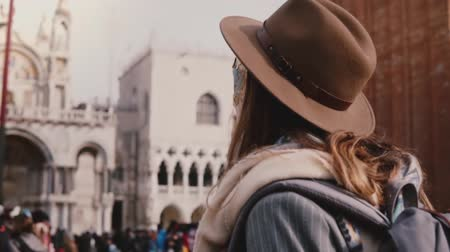 Венеция : Close-up back view shot of woman with long hair wearing stylish hat and carnival mask in San Marco, Venice slow motion.