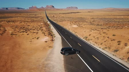 title : Drone follows silver minivan car taking and moving along iconic American desert highway road in Monuments Valley Arizona