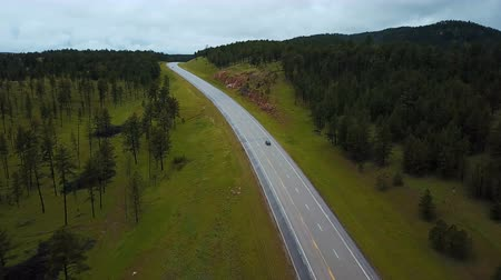 daleko : Beautiful aerial shot of silver car driving along American highway between wild green forest rocky hills with trees.
