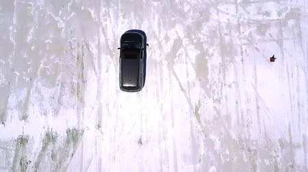 epik : Top view aerial drone shot of silver minivan car driving along incredible salt lake desert plain with amazing texture. Stok Video