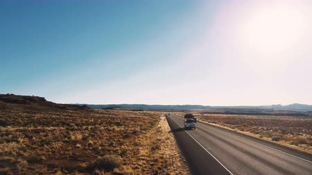 erosão : Drone flying low above typical American desert highway countryside road with cars passing by and amazing clear sky.