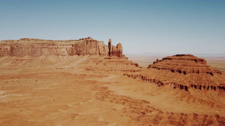 lifeless : Drone flying over sunny dry desert towards big rocky mountains and clear blue sky in Monument Valley national park.