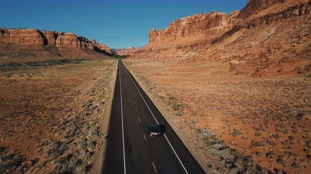 невероятный : Drone camera follows silver car moving along straight desert highway road among amazing rocky mountain landscape in USA. Стоковые видеозаписи