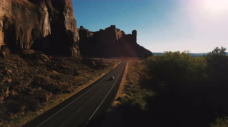 見落とす : Drone camera follows car driving along small desert highway road near breathtaking steep canyon ridge on sunset in USA.