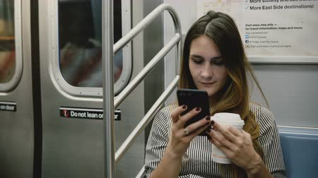 лидер : Happy relaxed attractive millennial girl sitting in subway train watching videos online on smartphone app and smiling.