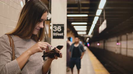 mensageiro : Beautiful young woman on the subway train platform holding smartphone and wallet making purchase on shopping online app. Stock Footage