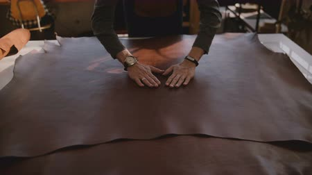 портной : Top view male artisan spreading and touching a big piece of brown leather material in manufacturing workshop slow motion