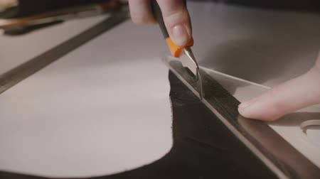 craftswoman : Close-up shot of hands working, cutting a big black piece of leather on a special table with tools, knife and ruler. Stock Footage