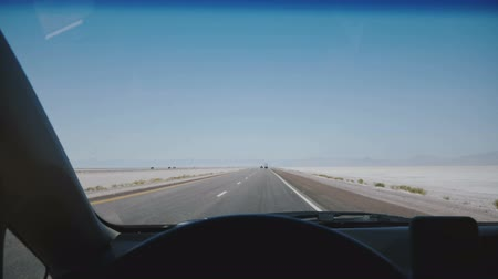 desert life : POV camera in car moving along amazing white salt lake desert road towards clear blue sky horizon at Bonneville Utah.