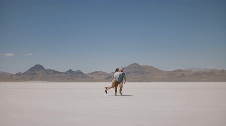 野心 : Back view young man walks towards beautiful woman standing and posing in the middle of sunny hot Utah salt desert lake.