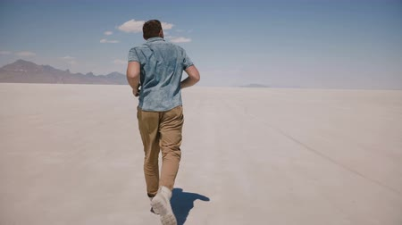 positive vibes : Camera follows young happy free man running forward enjoying amazing nature scenery at epic salt desert lake in Utah. Stock Footage