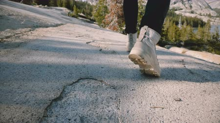 крепление : Close-up camera follows male legs in white desert shoes hiking alone at beautiful Yosemite forest rock slow motion. Стоковые видеозаписи