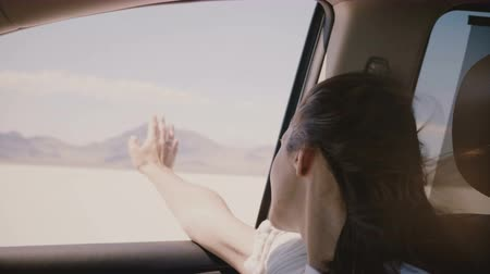 zavřít : Close-up shot of happy relaxed woman with hair blowing in the wind, eyes closed in car moving fast at salt lake desert.