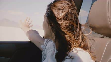 vibes : Close-up shot of happy young woman with flying hair and hand out of the window in car moving fast at salt lake desert.