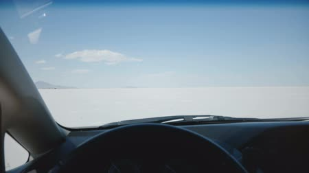 vibes : POV camera behind car steering wheel moving along amazing white salt lake desert flats towards clear sunny sky horizon.