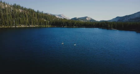 kano : Drone flying above epic large mountain lake with two kayakers rowing in the center at summer Yosemite national park.