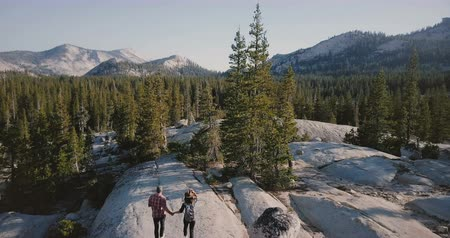 невероятный : Drone camera follows young happy couple run and hike together on amazing white rock towards epic Yosemite park skyline.