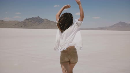 positive vibes : Camera follows beautiful young happy free woman running forward with arms open and flying hair at salt desert lake. Stock Footage