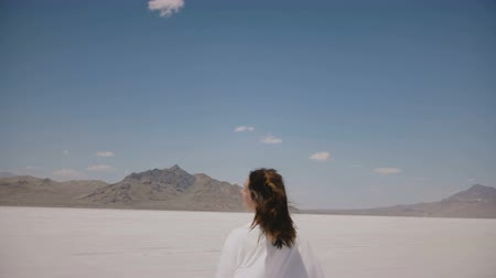 positive vibes : Camera follows young happy free woman running forward with hair blowing in the wind at sunny salt desert lake at Utah.