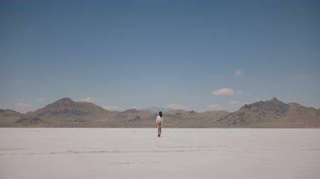 positive vibes : Beautiful background shot of woman walking from far away towards camera alone in deadly heat at salt desert lake in Utah
