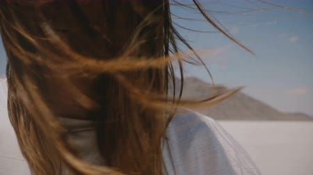 brackets : Super close-up lifestyle portrait of happy young woman smiling at camera with flying hair and braces at salt desert lake Stock Footage