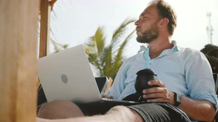 ноутбук : Low angle shot of successful happy comfortable freelancer man with laptop and drink resting in beach lounge resort chair Стоковые видеозаписи