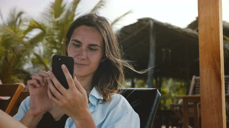 hírnök : Happy relaxed tourist woman resting in beach lounge chair using smartphone entertainment app on exotic vacation resort.
