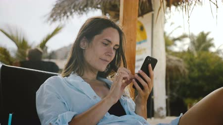 メッセンジャー : Happy relaxed tourist woman shopping online using smartphone app smiling, resting in exotic sea beach resort chair.