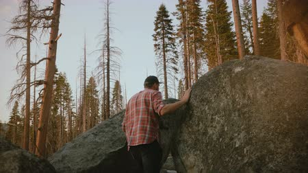 lumberjack : Camera follows young local man hiking, climbing up on big forest stones to watch epic sunset at Yosemite slow motion.