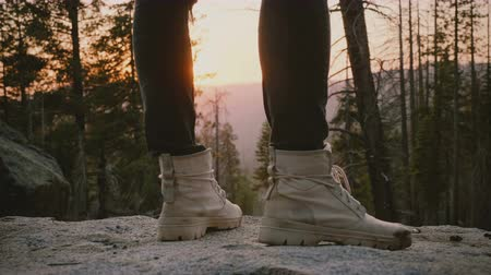 resistant : Close-up shot of male legs wearing grey desert shoes standing on a rock with epic forest sunset background slow motion.