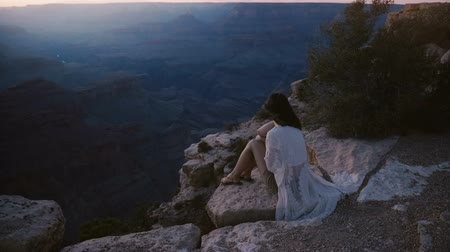nostalgisch : Slow motion cinematic shot of excited young woman with hair blowing in the wind sitting at epic sunset Grand Canyon. Stockvideo