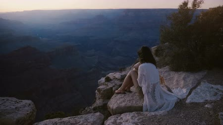 nostalgisch : Slow motion epic background shot of happy young woman with flying hair sitting at incredible Grand Canyon on sunset.