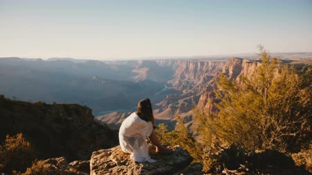 ностальгический : Camera moves up above peaceful young woman sitting at epic sunset panorama to reveal majestic Grand Canyon skyline.